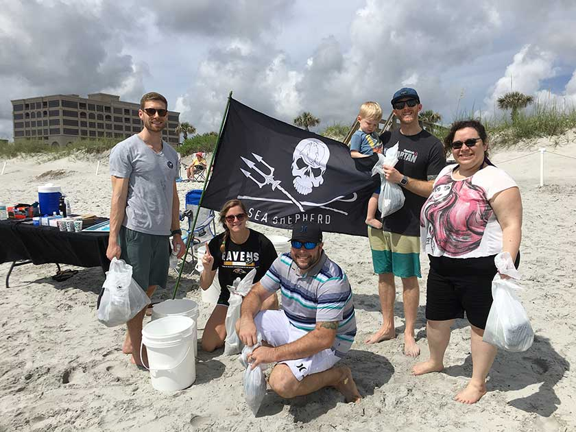 The MECLABS team participating in a beach cleanup